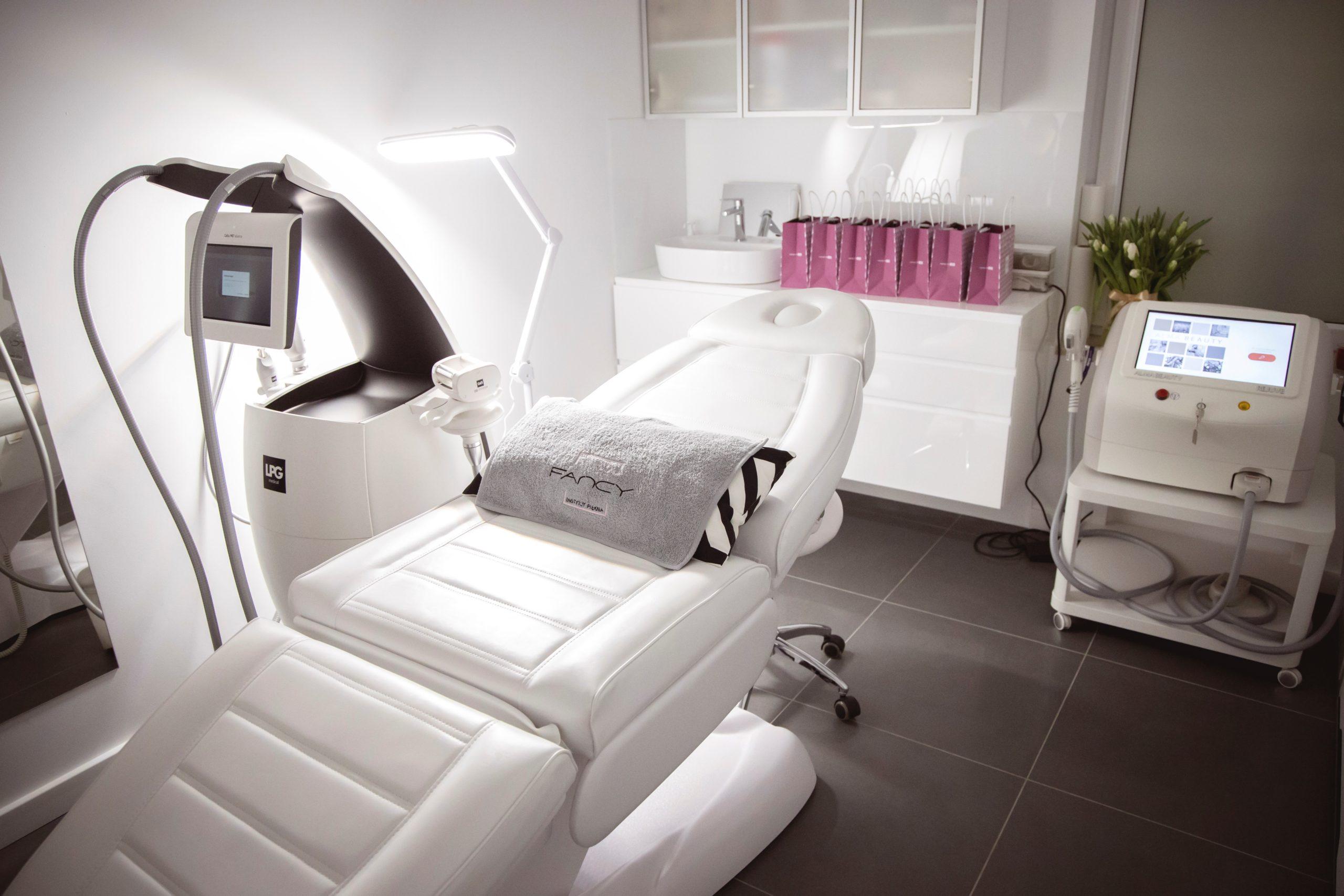 Zdjęcie przedstawia biały, rozkądany fotel w salonie usługowym